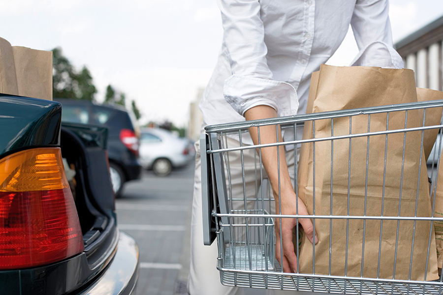 Person loading bagged groceries into car trunk